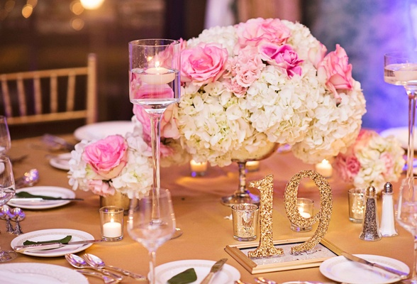 glittery gold table numbers with pink rose and white hydrangea centerpieces, floating candles