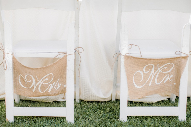 Outdoor wedding reception with white chairs and burlap Mrs. and Mr. signs