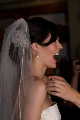 Side of bride's head with veil and red lips