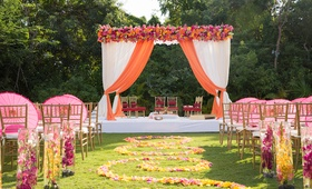 Outdoor Indian wedding ceremony with submerged yellow and magenta orchids along the aisle