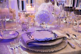 Wedding reception place setting silver charger plate with menu card candles low centerpiece rimmed