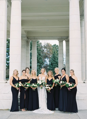 bride in berta wedding dress bridesmaids in mismatched black dresses gowns greenery bouquets