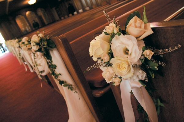 Yellow and cream roses tied to church pews