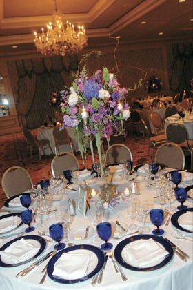 White table with blue glassware and purple centerpiece