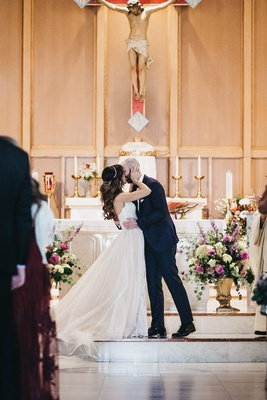 groom kisses bride during Roman Catholic church ceremony