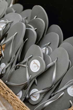 beach wedding favors at reception grey flip flops with white circle sticker tags in basket