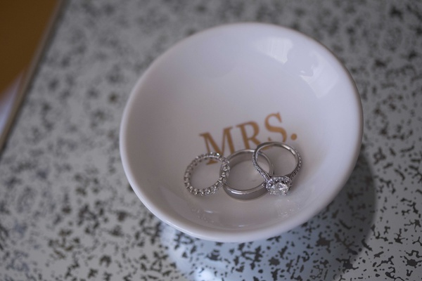 Wedding ring halo diamond engagement ring eternity band in white ceramic dish with MRS. in gold