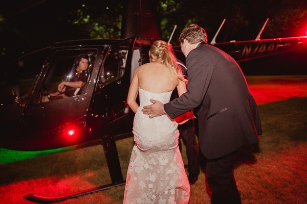 bride in mira zwillenger wedding dress gets on helicopter with groom to leave wedding