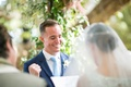 Groom in navy blue suit and light blue tie smiles and fist pumps yes gesture during wedding ceremony