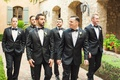 Groom in tuxedo and white boutonniere with groomsmen in rose boutonnieres at Silverleaf Club