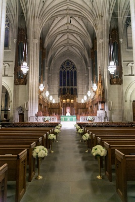 Wedding cathedral with white flower aisle decorations