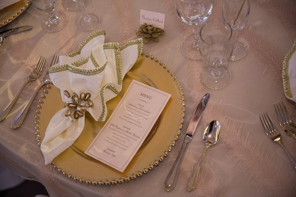 Wedding reception table with golden charger, menu, gilt embroidered napkins, pearl ties, succulent