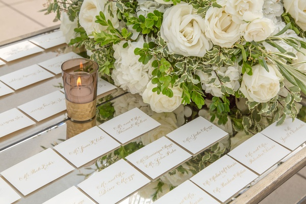 Mirror tabletop with gold calligraphy white escort cards white rose flower arrangement greenery