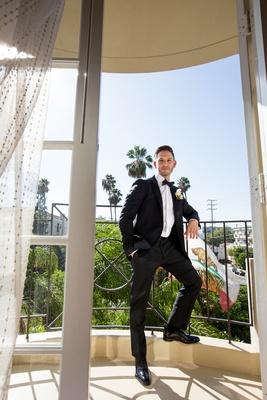 groom in lanvin tuxedo stands on balcony of hotel