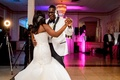 Bride in strapless wedding dress trumpet gown with groom in white tuxedo jacket bright pink lighting