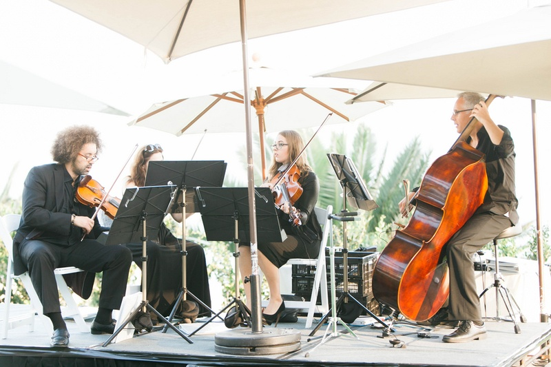 string quartet playing at the cocktail hour under umbrellas to block sun