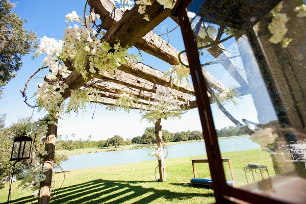 Wood arbor at ceremony with white flowers and chandelier