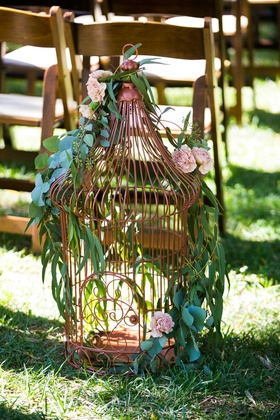a large copper lantern lining the aisle featuring winding green foliage and blush flowers