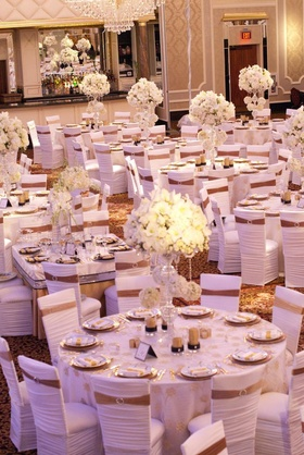 Wedding reception with white floral arrangements and chair sleeves with gold ribbons