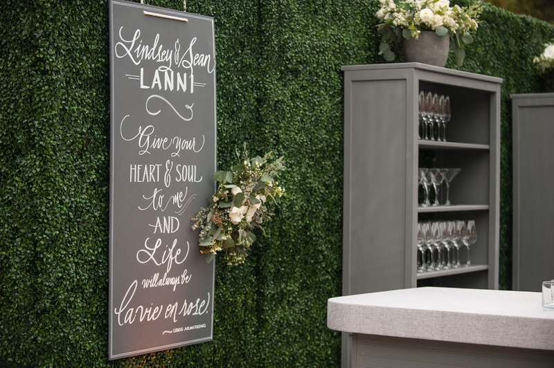 Outdoor Wedding Green Boxwood Hedge Wall Chalkboard Sign Louis Armstrong Quote Grey Bookshelf Bar
