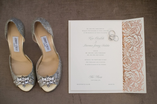 Silver Jimmy Choo heels, wedding bands, and invite