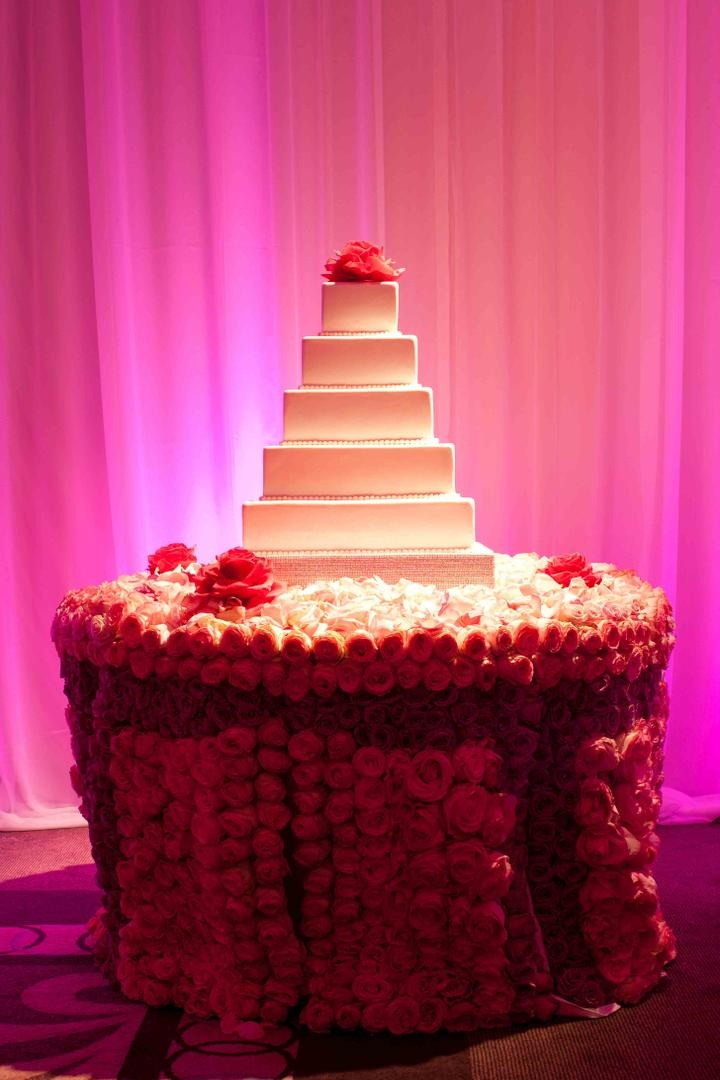 White wedding cake with pink camellia cake topper