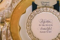 Wedding reception place setting with gold china and quote about the sea written in calligraphy