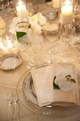 Table setting with orchids and candlelight on neutral tablecloth