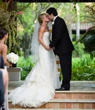 Bride and groom kissing on brick tile steps