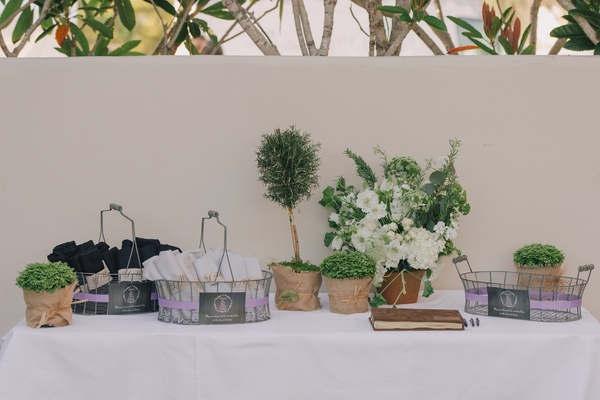 Small topiaries around silver baskets filled with favors