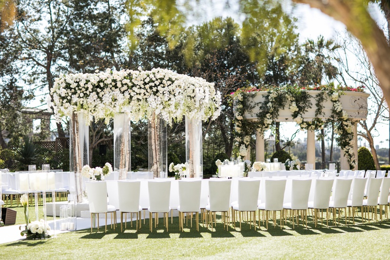 Guests seated in white chairs gold legs around chuppah birch branch white flowers greenery candles