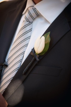 Groom's lapel with white tulip boutonniere and leaf