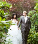 bride and groom in full wedding attire walk hand in hand through a garden during their first look