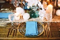 Bare wood table with gold rim glass charger plate, gold flatware, white orchid flowers, candles