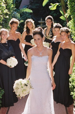 Bride with bridesmaids in black dresses outside