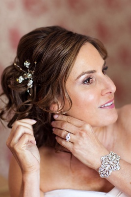 Bride wears floral hairpin and a rhinestone and pearl cuff bracelet