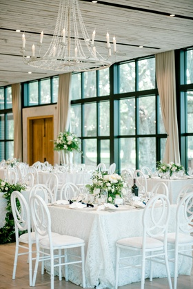 wedding reception floor to ceiling black frame windows wood door white table chairs high low flowers