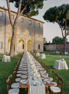long wooden table on lawn outside historic Italian building