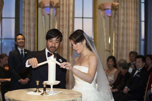 Bride and groom at wedding lighting pillar candle