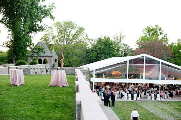 White tent with clear sides on lawn at beautiful venue