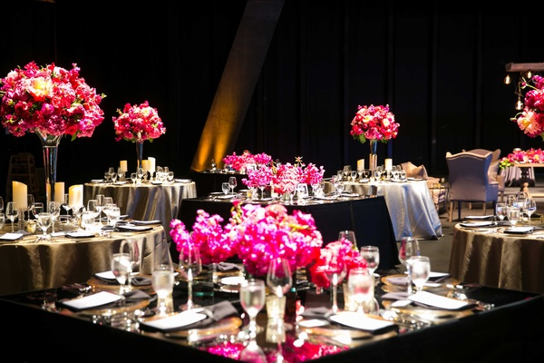 small square and circular tables with black and grey linens tall low bright pink florals dark space