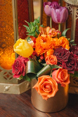 Orange roses and yellow tulips in gold vessel
