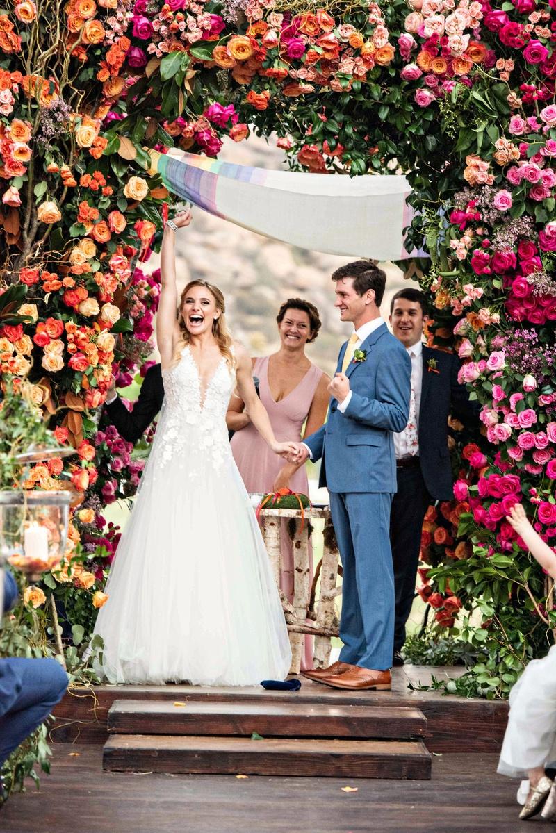 outdoor wedding ceremony wood aisle pink orange yellow purple red flower ceremony decor rainbow