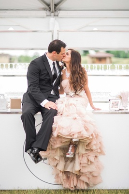 bride in blush vera wang mermaid ruffled gown, groom in black by vera wang tux, sit on bar