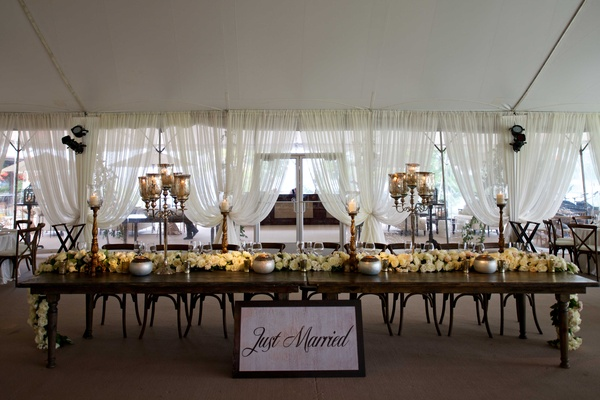 Tented wedding reception with long wood head table, rose table runner, Just Married sign, candelabra