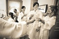 Black and white photo of bridesmaids in robes cheersing