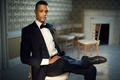stylish groom sitting chair wedding hempstead house new york classic look tux old-world vintage