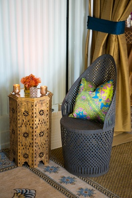 Metalwork chair with green, blue, yellow patterned throw pillow at Moroccan-style engagement party