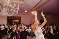 bride in mira zwillinger wedding dress and lace glovettes, bouquet toss