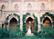 bride and groom posing under arches of bryn athel cathedral
